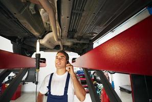 Mechaniker geht unter einem angehobenen Auto ans Telefon foto