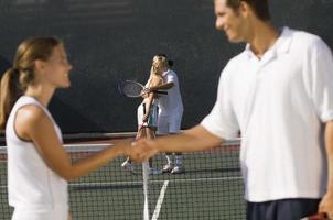 Tennisspieler Händeschütteln am Netz foto