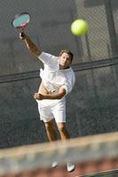 Tennisspieler trifft einen Schuss auf dem Platz foto