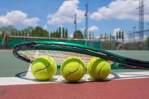 Tennisschläger und Bälle auf dem Tennisplatz foto