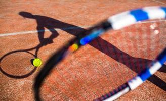 Schatten eines Tennisspielers in Aktion foto