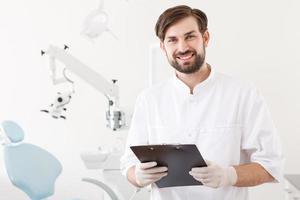 Porträt des jungen gutaussehenden Zahnarztes in der Klinik foto