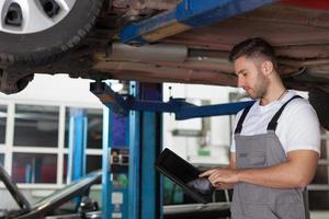 Arbeiten an einem digitalen Tablet unter dem Auto foto
