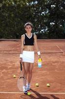 junges Mädchen, das Tennis auf dem Platz spielt foto