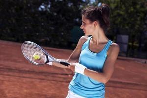 schönes junges Mädchen, das Tennis spielt foto