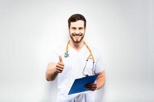 hübscher Arzt, der neben der Wand steht foto