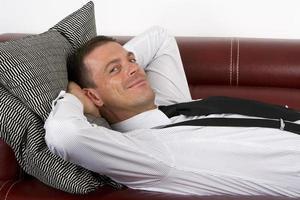 Geschäftsmann, der auf Couch liegt foto