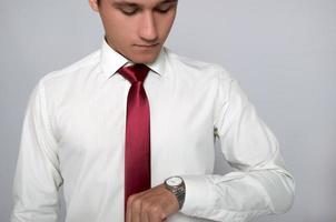junger Mann, der auf seine Armbanduhr schaut foto