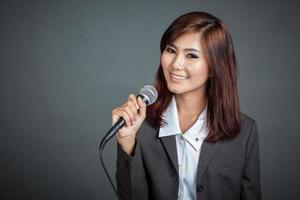 Nahaufnahme des asiatischen Geschäftsmädchens halten ein Mikrofon
