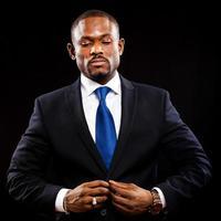 afrikanischer Geschäftsmann isoliert auf Schwarz, der seine Jacke anpasst foto