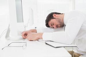 müder Geschäftsmann, der auf Tastatur schläft foto