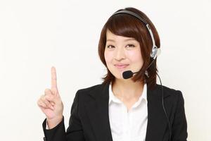 japanische Geschäftsfrau des Callcenters, die etwas präsentiert und zeigt foto