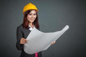 asiatische Ingenieurin Mädchen Lächeln halten eine Blaupause foto