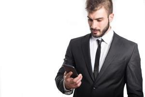 schöner Geschäftsmann, der eine SMS auf Smartphone liest foto