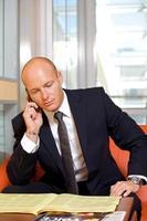 Geschäftsmann unterhält sich auf Handy beim Lesen der Zeitung foto