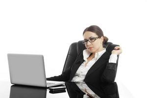 Frau in Gläsern sitzt hinter dem Schreibtisch und lächelt foto
