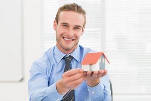 glücklicher Geschäftsmann, der Miniaturhaus zeigt foto