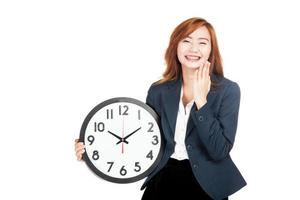 glückliche asiatische Geschäftsfrau, die mit einer Uhr lacht foto