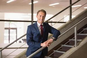 schöner Geschäftsmann, der auf Stufen steht foto