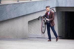 hübscher Geschäftsmann, der sein Fahrrad trägt foto
