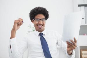 lächelnder Geschäftsmann, der Papier und Stift hält foto