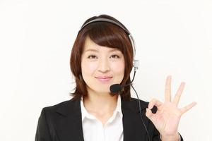 japanische Geschäftsfrau des Call Centers zeigt ein Siegeszeichen foto
