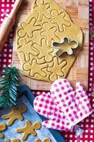 Schneiden des Lebkuchenplätzchenteigs für Weihnachten und Neujahr foto