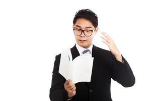 aufgeregter asiatischer Geschäftsmann las ein Buch foto