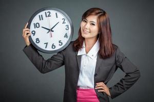 asiatische Geschäftsfrau halten eine Uhr und lächeln