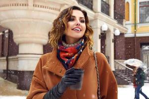 Frau mit Tasse Kaffee Spaziergang Schneestraße Weihnachten Neujahr foto