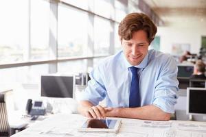 männlicher Architekt, der Tablet-Computer am Schreibtisch in einem Büro verwendet foto