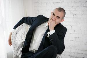 selbstbewusster lächelnder junger Geschäftsmann, der auf einem weißen Stuhl sitzt foto