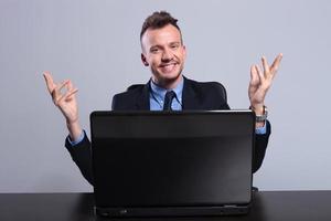 Geschäftsmann hinter Laptop begrüßt Sie foto