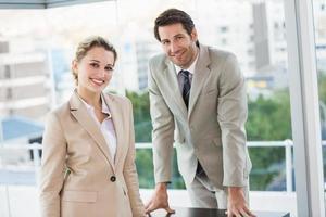 Geschäftsleute posieren und lächeln in der Kamera foto