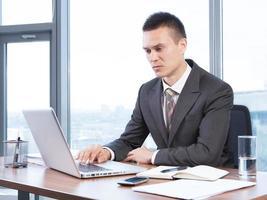 junger Geschäftsmann, der im Büro arbeitet foto