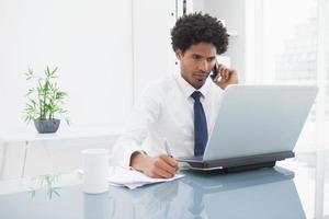 Geschäftsmann telefoniert und schreibt Notizen foto