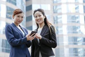Geschäftsfrauen sprechen vor Bürotürmen foto