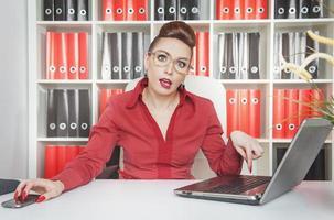 müde Geschäftsfrau, die mit Laptop arbeitet foto