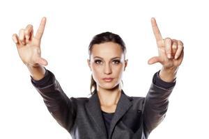 positive Geschäftsfrau zeigt mit ihren Fingern in der Lücke foto