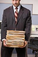 Geschäftsmann, der Stapel von Dateiordnern trägt foto