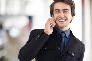 junger Mann, der Handy auf der Straße spricht foto