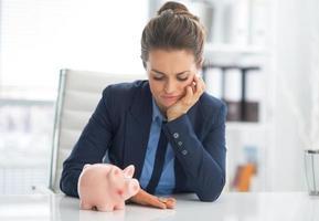 traurige Geschäftsfrau mit Sparschwein, das auf Münze schaut foto