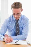 konzentrierter Geschäftsmann, der Notizen auf Notizbuch macht foto