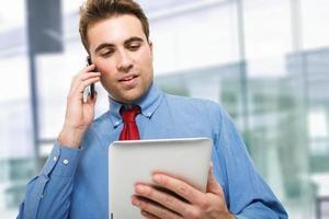junger Geschäftsmann, der am Telefon spricht foto
