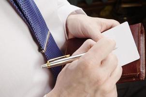 Geschäftsmann hält Blatt Papier und Stift foto