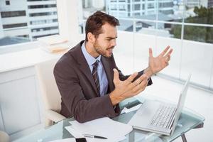 frustrierter Geschäftsmann, der Laptop im Büro benutzt foto