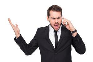 wütender Geschäftsmann, der am Telefon gestikuliert foto