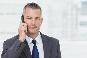 Geschäftsmann, der Kamera beim Telefonieren betrachtet foto