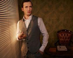 Retro-Mann mit einem Glas, das nahe Fenster steht. foto