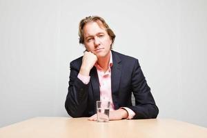Geschäftsmann mit blondem Haar sitzt gelangweilt hinter Schreibtisch. foto